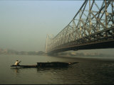 A Man Guides a Boat under a Bridge on the Hooghly River at Calcutta Lámina fotográfica por George, Ed
