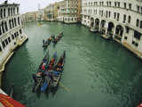 Gondolas Travel Down a Canal in Venice Photographic Print by Raul Touzon