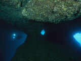 A Diver Explores an Underwater Formation Known as the Blue Hole Photographic Print by Tim Laman