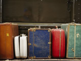 Colorful But Worn Luggage Awaits Travelers in a Train Station Photographic Print by Raul Touzon