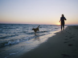 Woman and Dog Running on Beach, Nags Head, North Carolina Stampa fotografica di Brown, Skip