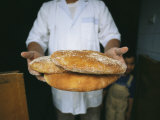 A Baker Shows His Fresh Loaves in the Village Bakery Photographic Print by Heather Perry