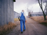 An Elderly Farmer in Overalls Walks Along a Dirt Road Past a Barn Photographic Print by Joel Sartore