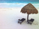 A Palm Frond Umbrella and Two Chairs on a White Sand Beach Photographic Print by Raul Touzon