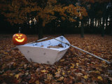 An Illuminated Jack-O-Lantern on the Back of a Rowboat Photographic Print by Bill Curtsinger