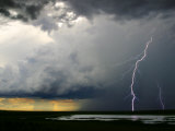 Lightning Cracks in a Cloud-Filled Sky with Rain Falling in Distance Photographic Print by Randy Olson