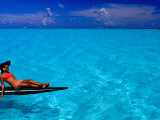 Woman Basking in the Sun on an Outrigger Boat in an Island Lagoon, Huahine Iti, French Polynesia Photographic Print by Jean-Bernard Carillet