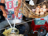 Basket of Eggs Hanging in Front of Woman Cooking Asian Stir-Fry, Rapid Creek Market, Australia Photographic Print by Will Salter