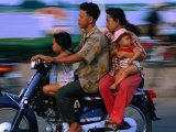 Young Family on Motorcycle., Phnom Penh, Cambodia Photographic Print by John Banagan