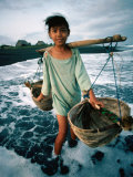 A Girl Gathers Salt Water in Lontar Leaf Buckets for Salt Making, Kusamba, Indonesia Photographic Print by Adams Gregory