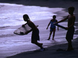 Young Surfers on Black-Sand Beach, French Polynesia Fotografisk tryk af Peter Hendrie