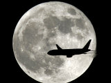 A Jet Plane Passes in Front of the Full Moon Above Surfside, Fla. Lmina fotogrfica