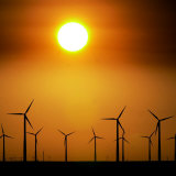 A Group of Wind Turbines are Silhouetted by the Setting Sun Photographic Print by Charlie Riedel