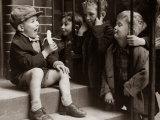 A Little Boy Holding a Banana Whilst Other Children Gaze Longingly at It Fotografická reprodukce