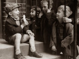 A Little Boy Holding a Banana Whilst Other Children Gaze Longingly at It Fotografie-Druck