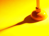 Red Rubber Plumbing Plunger in Yellow Light Photographic Print