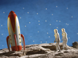 Astronaut Figurines Standing Beside Toy Rocket Photographic Print