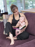 Woman Reading Book and Holding Baby in Living Room Photographic Print