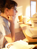 Young Woman Reading from Her Desktop Computer Screen and Studying Photographic Print