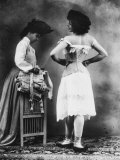 Lady Tries on a Corset While Another Woman Waits with Another One Photographic Print