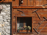 A Rich Wooden Wall with Rustic Tools and Window and a Stone Wall Photographic Print