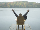 Man Sitting on a Dock with Arms Outstretched Photographic Print