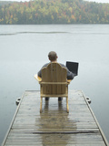 Man Sitting on a Dock Working on Laptop Photographic Print