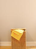 Yellow Towel in Wicker Laundry Basket Photographic Print