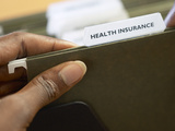 Woman Holding Health Insurance Folder Photographic Print