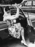 Girl in a Flower Print Dress, High Heels, Headscarf and Sunglasses Steps out of a Convertible Car Photographic Print