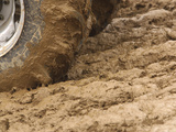 Tire Churning Through Mud Photographic Print