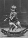 Little Boy on a Very Small Rocking Horse with a Whip in His Hand Photographic Print