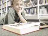 Little Boy Reading Book in Library Photographic Print
