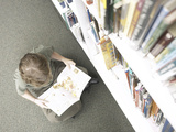 Little Boy Reading Book Beside Library Shelf Photographic Print
