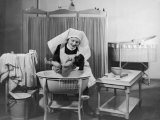 Uniformed Nurse Bathes a Baby in Hospital Photographic Print