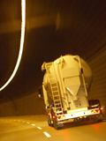 White Tanker Truck Driving Through Tunnel Lit with Electrical Lighting Photographic Print