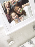 Smiling Family Brushing Their Teeth Together in Bathroom Mirror Photographic Print