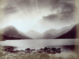 A Lake Surrounded by Mountains in a Stormy Dawn Photographic Print