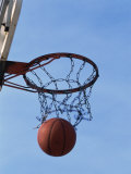 Low Angle View of a Basketball Going Through The Hoop Photographic Print