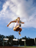 Low Angle View of a Female Athlete Jumping Over a Hurdle Photographic Print