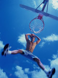 Low Angle View of a Young Man Slam Dunking a Basketball Photographic Print