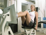 Young Woman Exercising on a Machine in a Gym Photographic Print