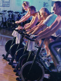 Group of People on Exercise Bikes in a Health Club Photographic Print