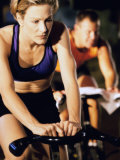 Young Woman Exercising on a Cycling Machine Photographic Print