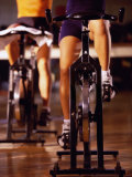 Low Section View of Two People Cycling in a Health Club Photographic Print