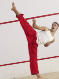 Young Man Kicking While Practicing Karate Photographic Print