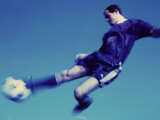 Soccer Player Jumping in Mid Air to Kick a Soccer Ball Photographic Print