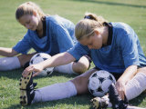 Teenage Girls in Soccer Uniforms Doing Stretching Exercises Photographic Print