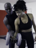Trainer Helping Young Woman Exercise with Weights Photographic Print