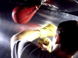Rear View of a Boxer Punching a Punching Bag Photographic Print